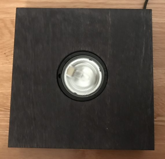 A square wooden lamp base, with one central, recessed LED light.