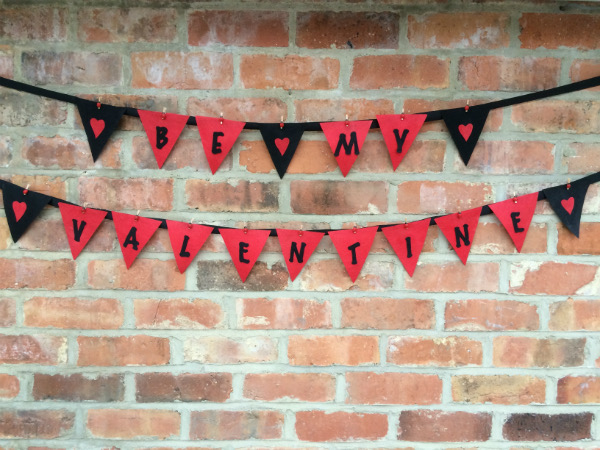 'Be my Valentine' in black lettering on red triangular flags of bunting, hung on black ribbon against a brick wall. Black flags with red hearts appear at the beginning, in between and at the end of the words.