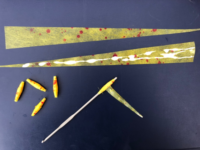 Two long thin triangles of yellow coloured Zeelon covered with a smattering of red dots. One triangle has been covered in a trail of white glue. A crochet hook is pictured rolling up another triangle into a bead shape. Four finished beads are also present.