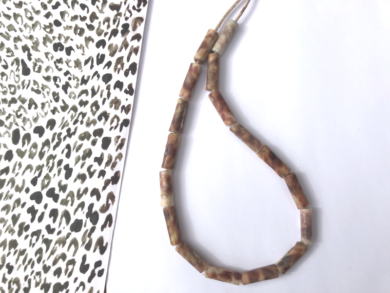 A necklace of straight mottled coloured brown beads on a beige leather strand.
