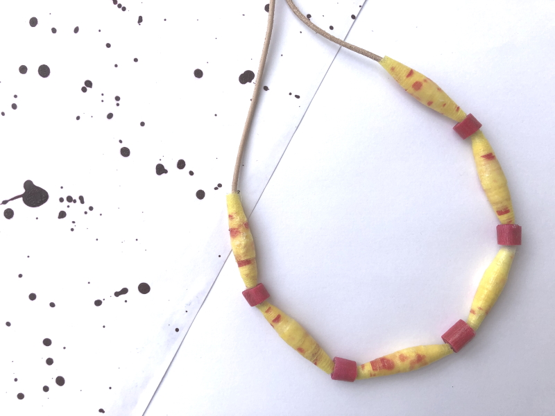 A string of yellow and red patterned beads, interspersed with small plain red beads.