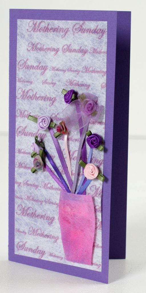A tall purple card with a centre panel of Lutradur 100gsm, printed all over with the words 'Mothering Sunday' in a script font of varying sizes. A small vase has been cut from Lutradur 70, painted pink and positioned in the lower righthand corner. Inside the vase are eight straight strands of ribbon, below small 'balls' of  contrasting wound ribbon to represent flowers, in various shades of purple, mauve and pink.