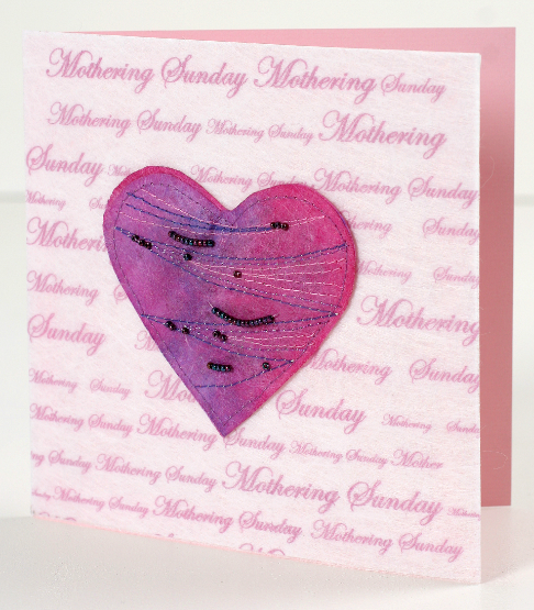 A pink square card covered with Lutradur 100gsm which has been printed all over with the words 'Mothering Sunday' in a script font of varying sizes. In the centre of the card is a deep pink heart which has been embellished with strands of very small dark beads and zigzag rows of blue machine stitching.
