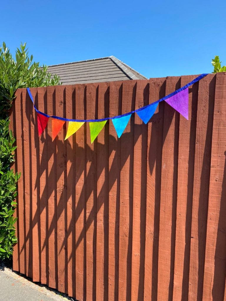Very similar to previous photograph, but this time the rainbow bunting has been sewn on to Royal blue ribbon.