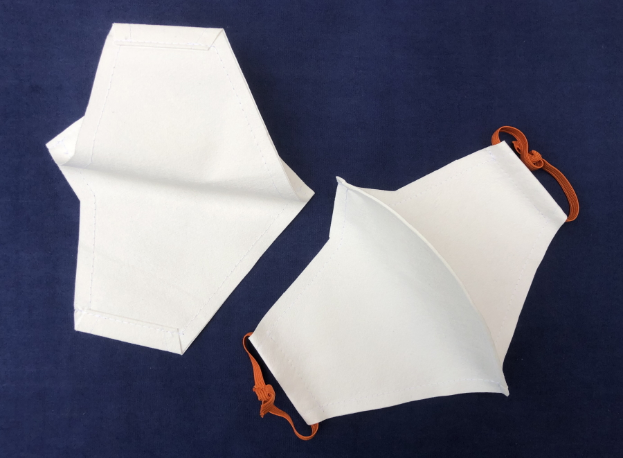 Two masks, one showing the inside where the side seams have been sewn. The other viewed from the outside, with orange loops of elastic threaded through the side seams.