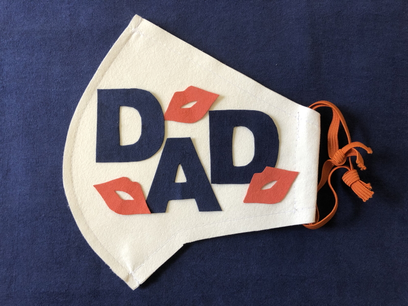 White Evolon face mask embellised with the word DAD in dark blue lettering and decorated with three sets of red lips.