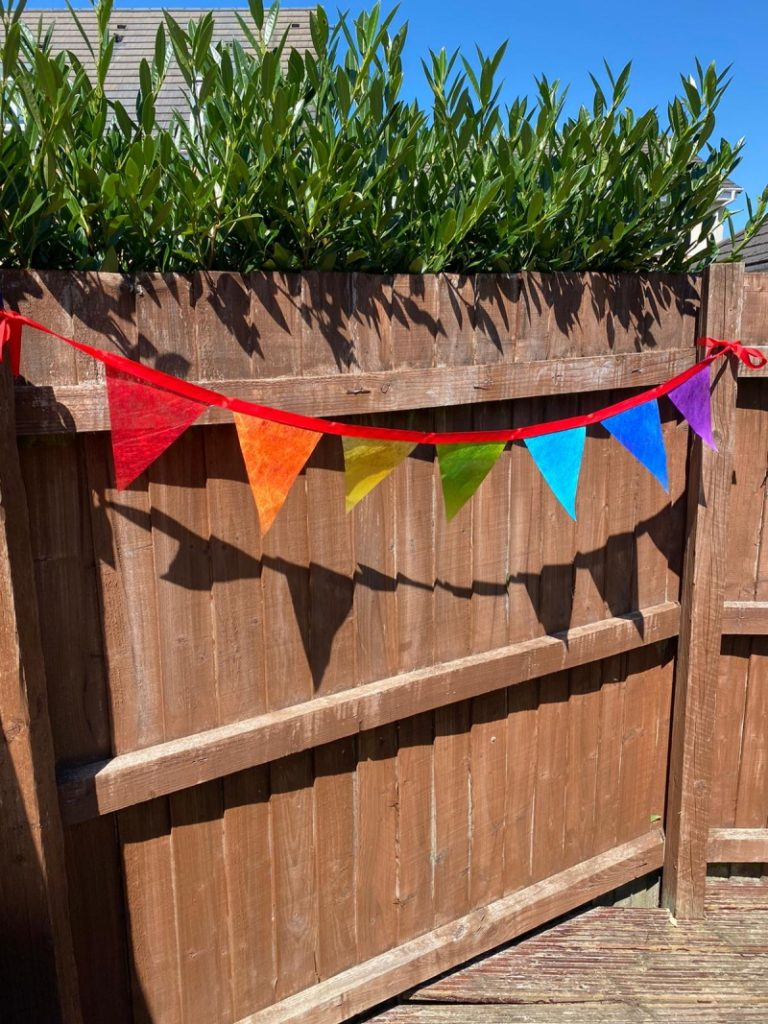 Line of bunting with seven triangular flags machine stitched on to a bright red ribbon. Each flag is one of the colours of the rainbow and arranged in sequence, i.e. red, orange, yellow, green, blue, indigo and violet. The bunting is hung against a brown wooden fence.