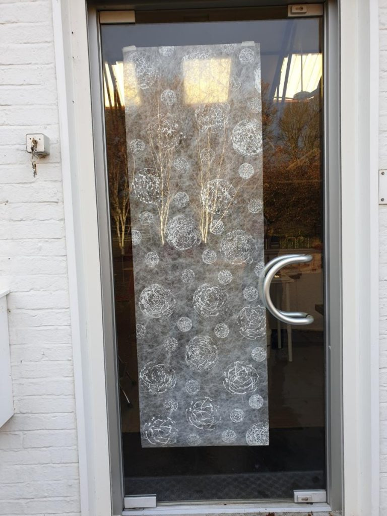 Solid glass door with large semi-circular metal handle on the right.  Stuck to the inside of the door is a long panel of white Lutradur decorated all over with open 'stringy' type balls in large and small sizes.