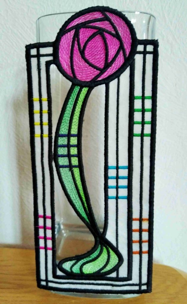 Tall glass vase decorated with machine embroidered Rennie Mackintosh panel.  The panel has a large round pink Art Deco rose at the top, above a tapered curved green stem. The rose is surrounded by several straight black lines which form a sort of window frame.