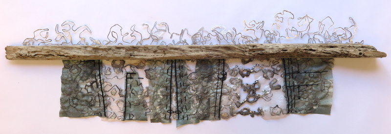 A long thin piece of horizontal driftwood, with thin wire 'waves' attached to the top surface. Four rectangular pieces of dark coloured Evolon hang from the underside, embellished with machine stitching and joined together with more wire and bits of plastic.