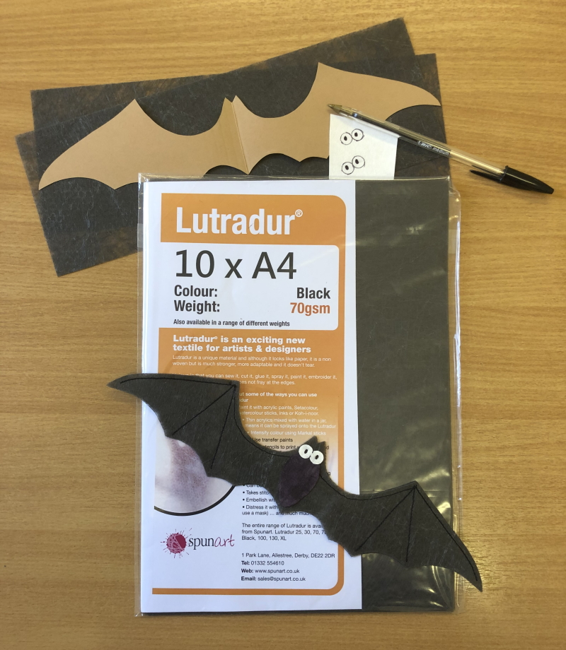 An A4 pack of Lutradur 70gsm Black, a cardboard bat template, a completed bat, a small piece of Evolon and a black biro.