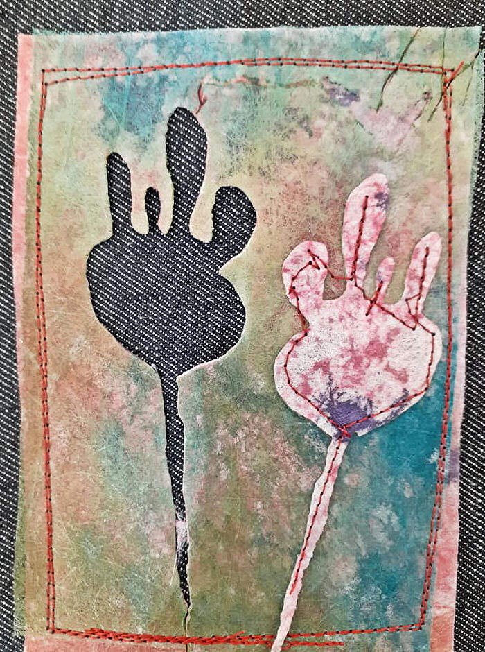 A rectangular piece of Lutradur painted all over in soft muted colours. On the left-hand side of the Lutraudr, the shape of a poppy seed head on a stem has been cut out and then it has been stitched to the right hand side of the Lutradur. Both the background and the cut out have been sewn on to a dark denim background using red thread.