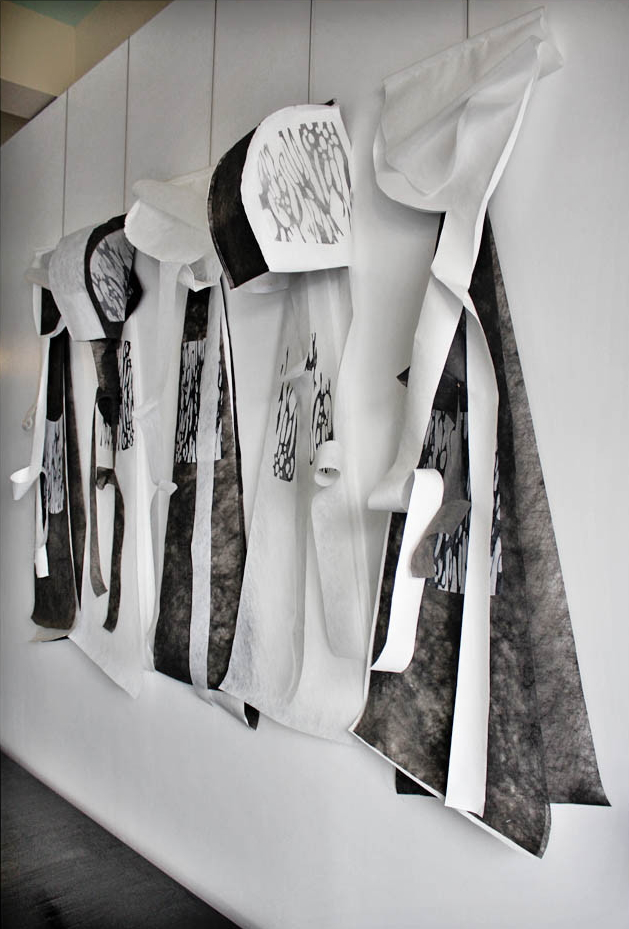 Wall hung display representing five capes with hoods. Some of the hoods are projecting outwards, while others are laid flat. The capes are made up of layers of black and white material and feature some areas of decorative printed design.
