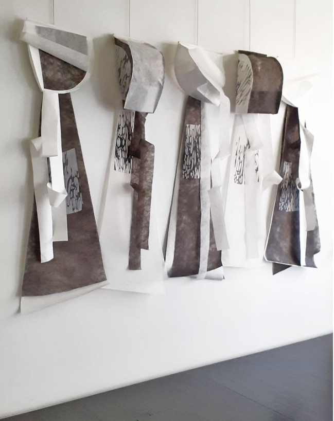 Five black and white capes hanging on a wall. They each feature a rectangular area of printed design and large curved hoods.