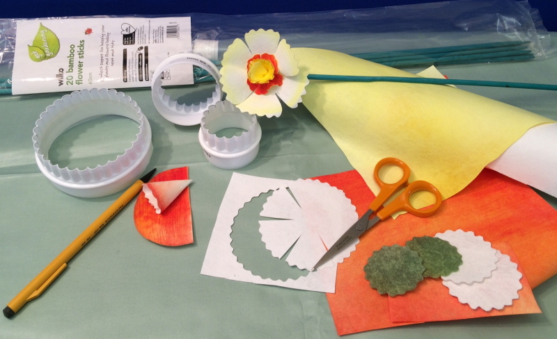 Picture of the materials used to make our daffodils, i.e. three white plastic fluted pastry cutters, a pencil, pair of orange handled scissors, yellow, orange and white pieces of Evolon and some green garden sticks. A finished daffodil can be seen in the centre of the photograph.