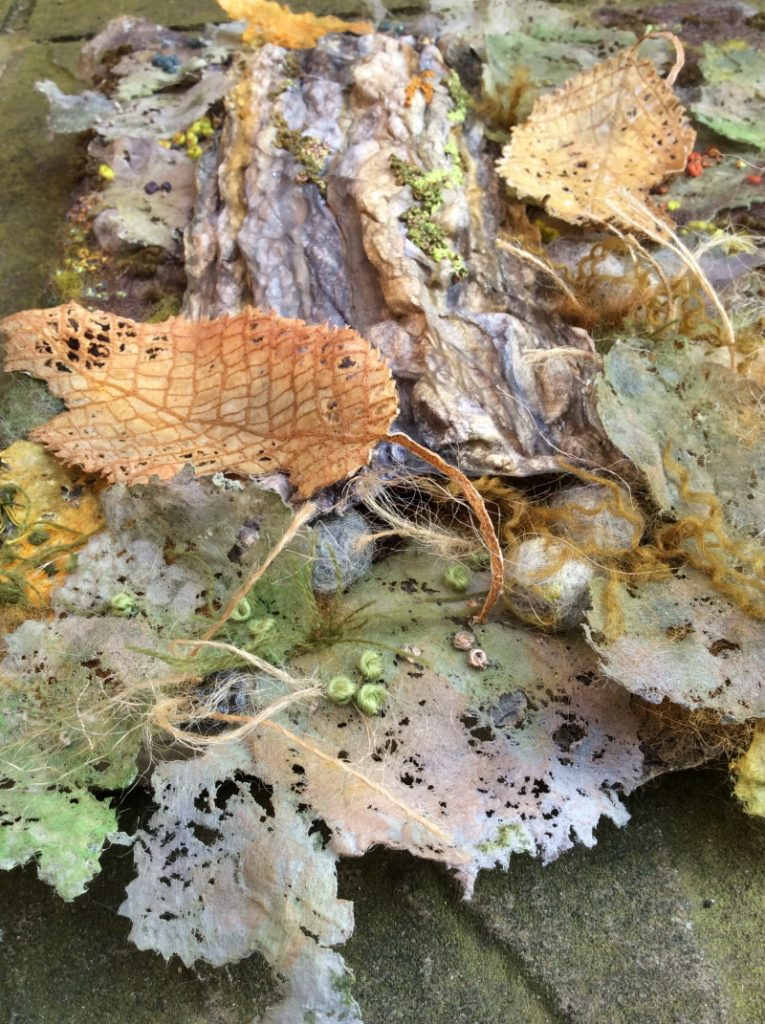 Close up photograph of textiles used to create the appearance of a forest floor. i.e. fallen leaves, tree bark, moss and seeds. Subtle shades of light orange, green and lilac along with wispy textures have been used to make a very realistic piece of work.