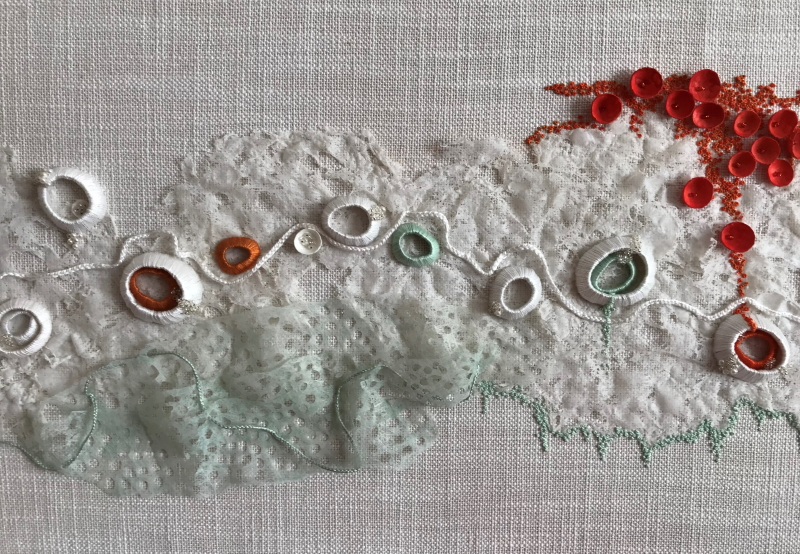 Light grey cloth background with row of limpet type shells, wrapped in orange, white and green silk thread, randomly spread across the central section. The shells rest on a foam of Lutradur 100, which has been coloured with light green acrylic paint and punctured with small holes created with a soldering iron. A spray of small red discs which resemble acorn cups, decorate the top right section of the piece.